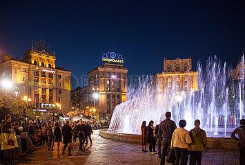 Passanten und beleuchtete Springbrunnen auf dem Maidan in Kiew