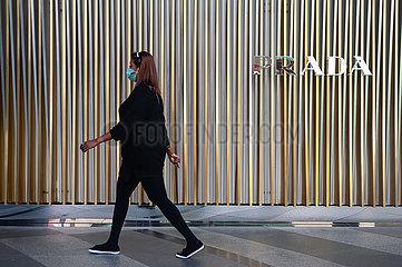 Singapur  Republik Singapur  Frau mit Mundschutz geht an einem Geschaeft von Prada vorbei