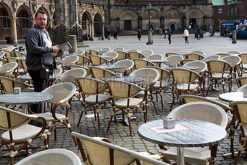 Deutschland  Bremen - Flaute durch Corona  sorgennvoller Blick eines Kellners eines Cafes am Marktplatz