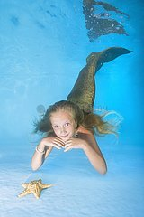 Young beautiful girl lies and smiling on the bottom of the swimming pool. underwater girls pictures