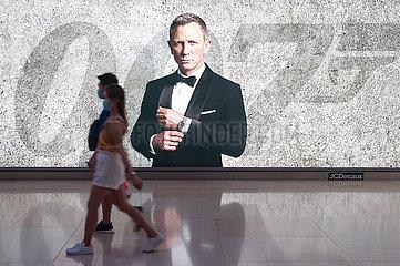 Singapur  Republik Singapur  Personen mit Mundschutz vor einer Werbung fuer James Bond Film