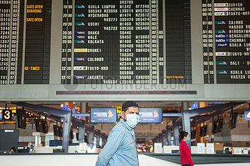 Singapur  Republik Singapur  Mann mit Mundschutz vor Anzeigetafel am Flughafen Changi
