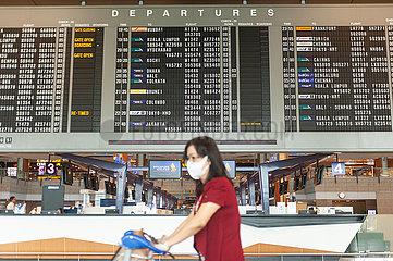Singapur  Republik Singapur  Frau mit Mundschutz vor Anzeigetafel am Flughafen Changi