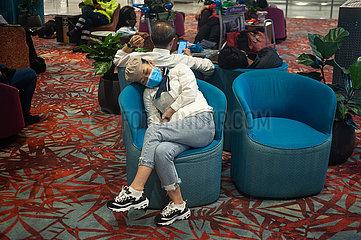 Singapur  Republik Singapur  Wartende Flugreisende schlaeft am Flughafen Changi im Sessel
