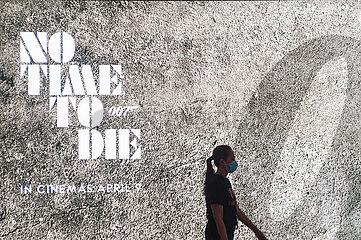 Singapur  Republik Singapur  Frau mit Mundschutz vor einer Werbung fuer James Bond Film
