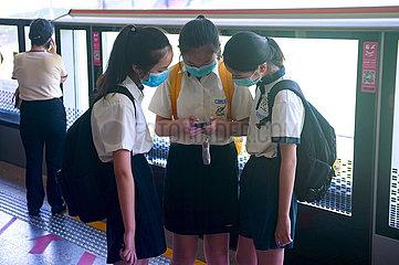 Singapur  Republik Singapur  Schuelerinnen mit Mundschutz warten am Bahnsteig auf die Bahn