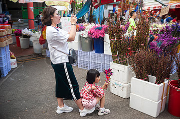 Singapur  Republik Singapur  Eine Frau fotografiert mit ihrer Tochter auf dem Fuss sitzend