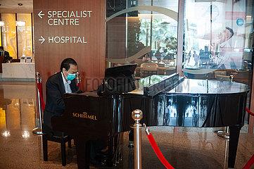 Singapur  Republik Singapur  Ein Pianist mit Mundschutz spielt im Foyer eines Krankenhauses Fluegel