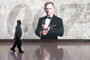 Singapur  Republik Singapur  Mann mit Mundschutz vor einer Werbung fuer James Bond Film