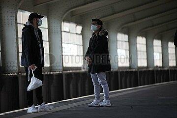 Zwei junge Maenner mit Atemschutzmaske