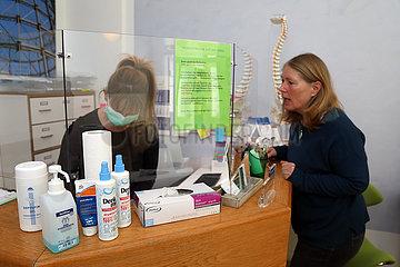 Berlin  Deutschland  Physiotherapeutin vereinbart geschuetzt hinter einer Glaswand einen medizinisch notwendigen Termin mit einer Patientin