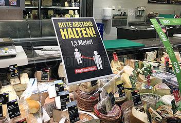 Berlin  Deutschland  Auswirkungen des Coronavirus: Bitte in einem Supermarkt auf das Einhalten des Sicherheitsabstandes von 1 5 Meter zwischen den Kunden