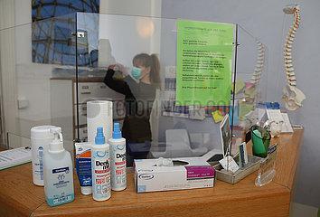 Berlin  Deutschland  Physiotherapeutin arbeitet aufgrund der Corona-Krise am Empfangstresen hinter einer Glaswand. Desinfektionsmittel stehen in ausreichender Zahl davor