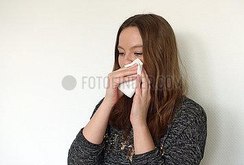 Berlin  Deutschland  junge Frau putzt sich die Nase