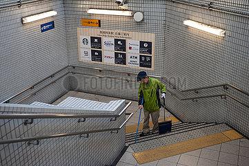 Kyoto  Japan  Mann fegt die Treppe einer U-Bahnstation