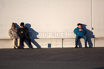 Deutschland  Bremerhaven - Rentner geniessen Sonnenuntergang an der Muendung der Weser in die Nordsee und halten den durch Corona gebotenen Abstand
