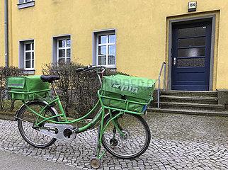 Berlin  Deutschland  Fahrrad des Postzustellers PIN AG steht vor dem Eingang eines Mehrfamilienhauses
