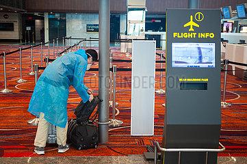 Singapur  Republik Singapur  Passagier mit Mundschutz und Regenmantel vor dem Check-in am Flughafen Changi
