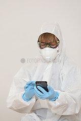 Berlin  Deutschland  gestellte Szene: Aerztin in Schutzkleidung schaut auf ihr Mobiltelefon