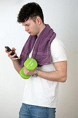 Berlin  Deutschland  Teenager trainiert mit einer Hantel und schaut dabei auf sein Smartphone