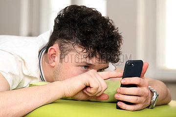 Berlin  Deutschland  Teenager tippt im Bett auf seinem Smartphone herum