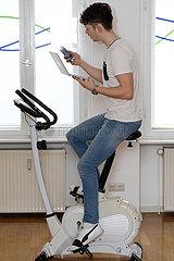 Berlin  Deutschland  Teenager sitzt auf einem Hometrainer und schaut dabei auf sein Tablet und Smartphone