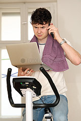 Berlin  Deutschland  Teenager sitzt telefonierend auf einem Hometrainer und schaut dabei zweifelnd auf sein Tablet