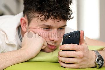 Berlin  Deutschland  Teenager schaut im Bett gelangweilt auf sein Smartphone