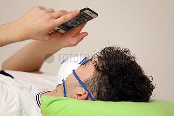 Berlin  Deutschland  junger Mann mit Atemschutzmaske schaut auf sein Mobiltelefon
