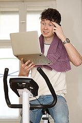 Berlin  Deutschland  Teenager sitzt telefonierend auf einem Hometrainer und schaut dabei auf sein Tablet