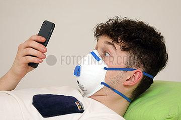 Berlin  Deutschland  junger Mann mit Atemschutzmaske schaut ueberrascht auf sein Mobiltelefon