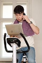 Berlin  Deutschland  Teenager sitzt telefonierend auf einem Hometrainer und schaut dabei ueberrascht auf sein Tablet