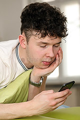 Berlin  Deutschland  Teenager schaut im Bett auf sein Smartphone