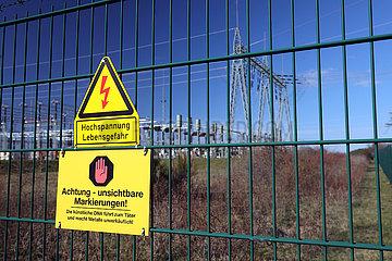 Nunsdorf  Deutschland  Hinweisschilder - Kuenstliche DNA - und - Hochspannung Lebensgefahr - am Zaun eines Umspannwerks