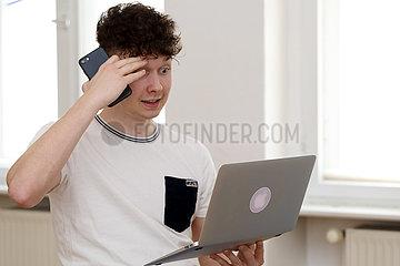Berlin  Deutschland  Teenager haelt sein Smartphone in der Hand und schaut fassungslos auf sein Tablet