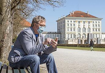 aelterer Mann mit Munschutz  Nymphenburger Schlosspark  Muenchen  April 2020
