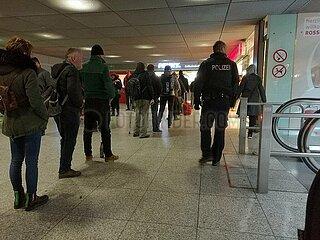 Polizist ueberwacht Warteschlange vor Supermarkt