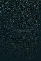 Berlin  Deutschland - Regentropfen an der Fensterscheibe vor dunklem Hintergrund.