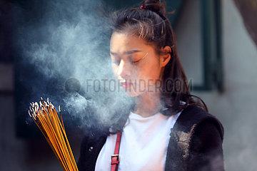 Macau  China  junge Frau betet im A-Ma Tempel mit angezuendeten Raeucherstaebchen