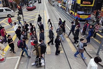 Hongkong  China  Menschen uberqueren eine Strasse