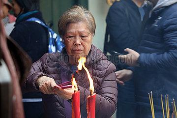 Macau  China  alte Frau zuendet im A-Ma Tempel Raeucherstaebchen an