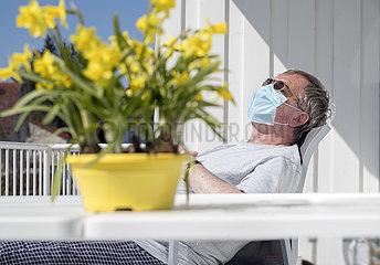 aelterer Mann mit Munschutz sonnt sich auf seinem Balkon  Muenchen  April 2020