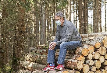 aelterer Mann mit Mundschutz  Pause bei Spaziergang im Wald  Muenchen  April 2020