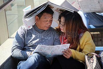 Hongkong  China  eine Zeitung dient Mann und Frau als Sonnenschutz