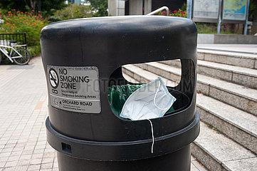 Singapur  Republik Singapur  Weggeworfener Mundschutz in einem Muelleimer