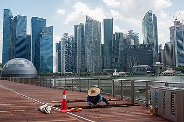 Singapur  Republik Singapur  Arbeiter vor der Skyline des Geschaeftsviertels am Ufer in Marina Bay