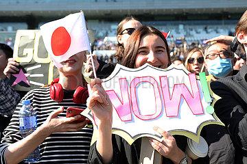 Hongkong  China  Frau haelt laechelnd eine Japanische Nationalfahne und ein Schild mit der Aufschrift WOW in den Haenden