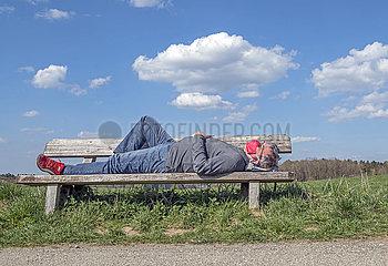 aelterer Mann mit Mundschutz schlaeft auf Parkbank  Glonn  April 2020
