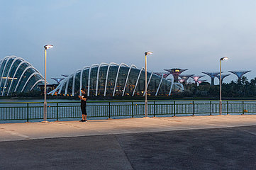 Singapur  Republik Singapur  Frau in Marina Bay mit Gardens by the Bay im Hintergrund