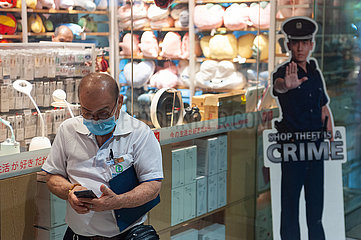Singapur  Republik Singapur  Mann mit Mundschutz starrt auf sein Handy